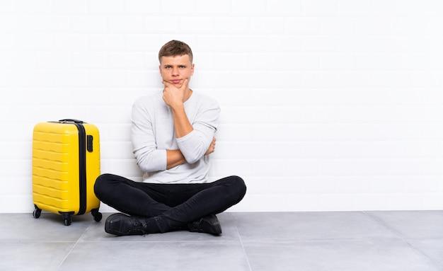 Jeune bel homme assis sur le sol avec une valise en riant