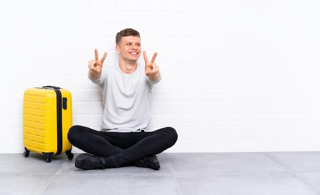 Jeune bel homme assis sur le sol avec une valise en souriant et en montrant le signe de la victoire