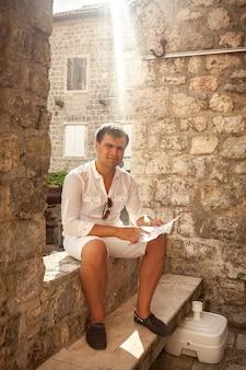 Jeune bel homme assis sur la vieille rue et tenant la carte dans les mains