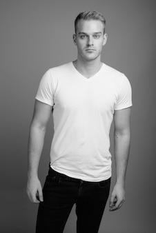Jeune bel homme aux cheveux blonds contre un mur gris en noir et blanc
