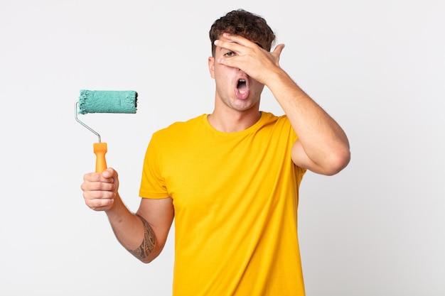 Jeune bel homme ayant l'air choqué, effrayé ou terrifié, couvrant le visage avec la main. concept de maison de peinture