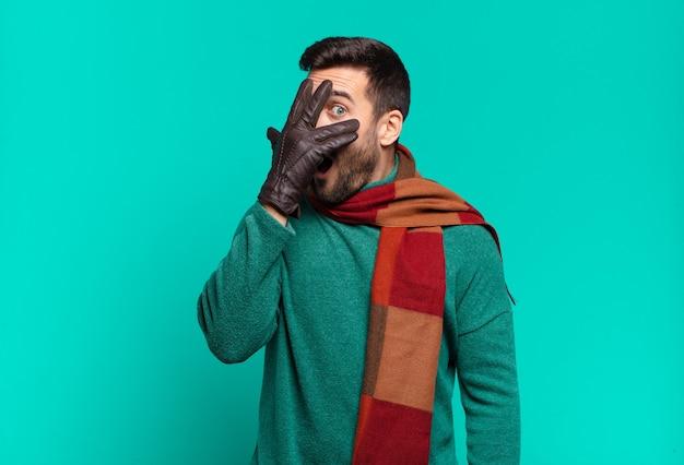 Jeune bel homme ayant l'air choqué, effrayé ou terrifié, couvrant le visage avec la main et regardant entre les doigts. conception froide et hivernale