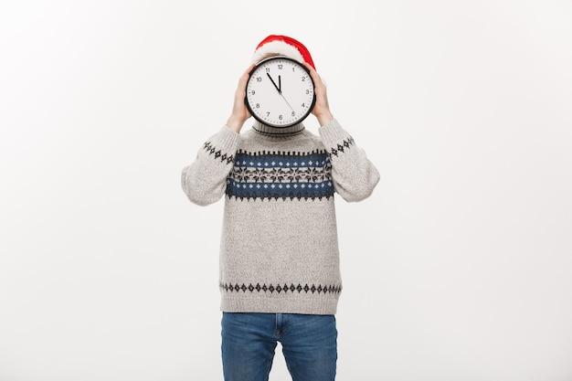 Jeune bel homme barbe caché derrière une horloge blanche sur blanc