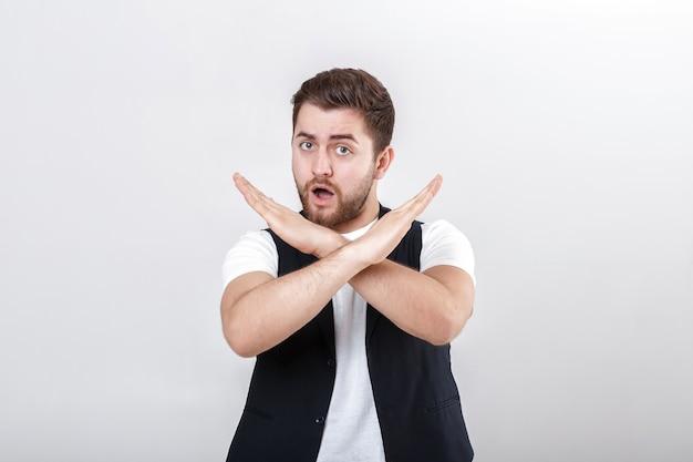 Le jeune bel homme avec une barbe dans une chemise blanche et un gilet noir montre l'arrêt de geste