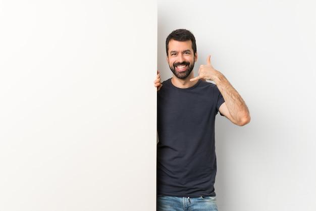 Jeune bel homme à la barbe faisant un geste de téléphone