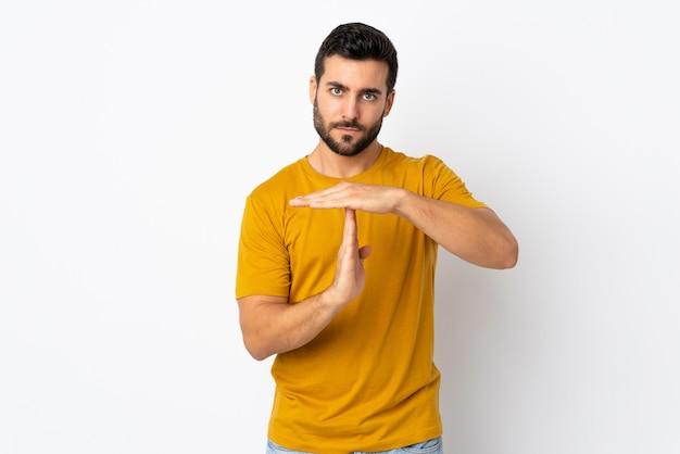 Jeune bel homme avec barbe isolé sur blanc faisant le geste de délai d'expiration