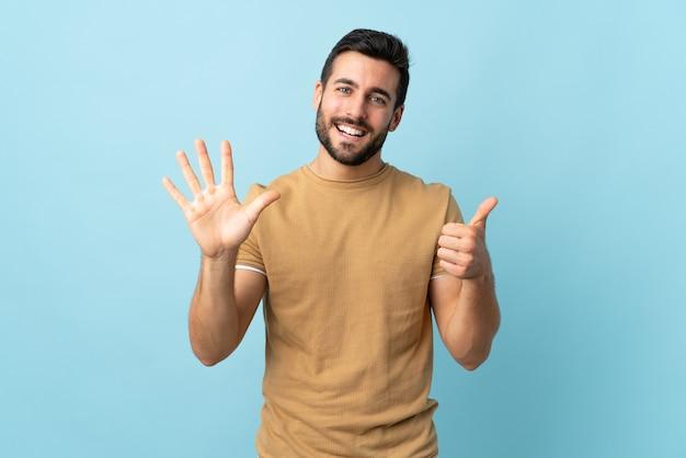 Jeune bel homme avec barbe isolé comptant six avec les doigts