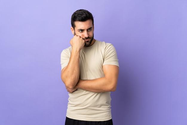Jeune bel homme avec barbe sur isolé avec une expression fatiguée et ennuyée