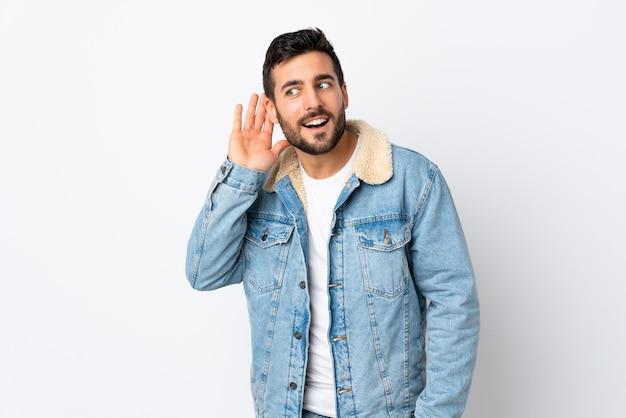 Jeune bel homme avec barbe isolé sur un mur blanc en écoutant quelque chose en mettant la main sur l'oreille