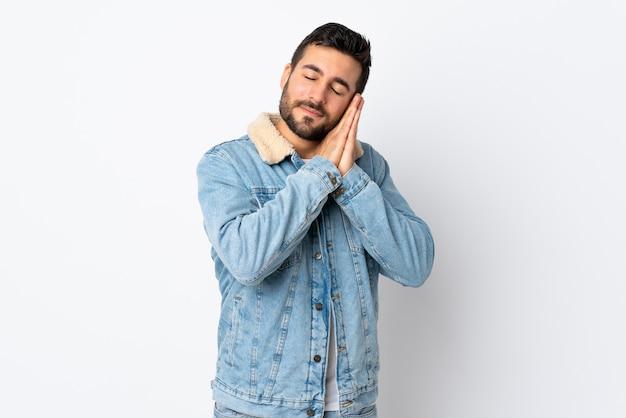 Jeune bel homme avec barbe isolé sur mur blanc faisant un geste de sommeil dans une expression dorable