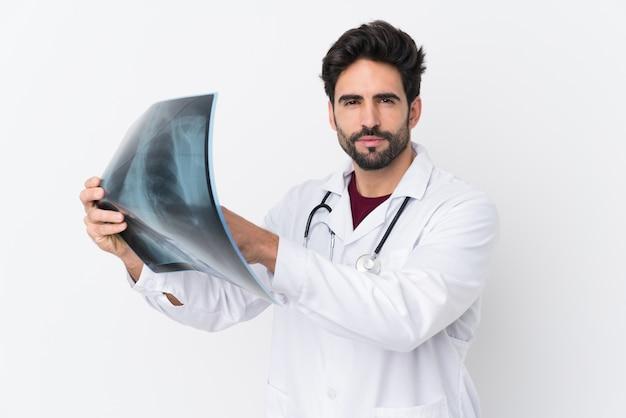 Jeune bel homme avec barbe sur mur blanc isolé portant une robe de médecin et tenant une scintigraphie osseuse