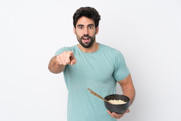 Jeune bel homme avec barbe sur mur blanc isolé surpris et pointant vers l'avant tout en tenant un bol de nouilles avec des baguettes
