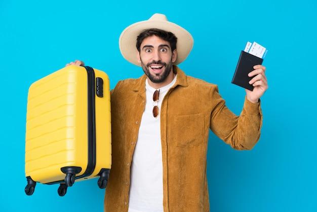 Jeune bel homme avec barbe sur mur bleu isolé en vacances avec valise et passeport et surpris