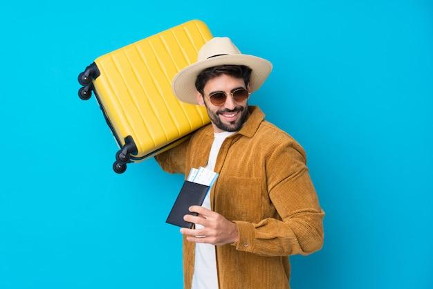 Jeune bel homme avec barbe sur mur bleu isolé en vacances avec valise et passeport