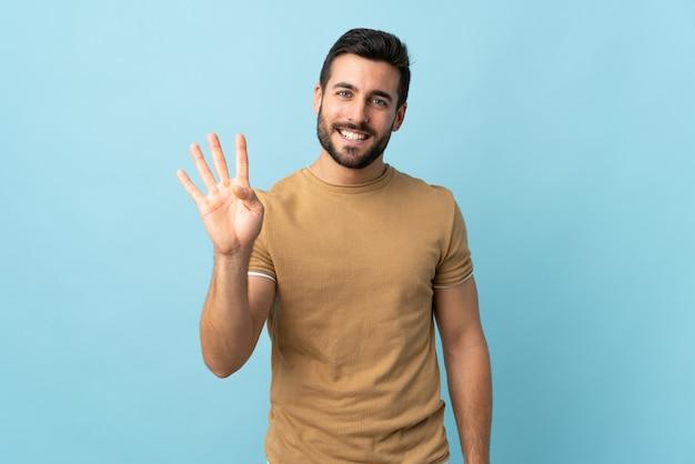 Jeune bel homme avec barbe sur mur isolé heureux et comptant quatre avec les doigts