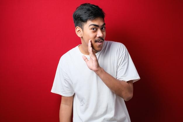 Jeune bel homme à la barbe portant un t-shirt blanc et des lunettes sur fond rouge main sur la bouche racontant une rumeur secrète, chuchotant une conversation malveillante