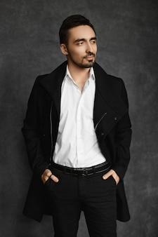 Jeune bel homme avec une barbe soignée et une moustache dans un manteau noir et une chemise blanche regardant de côté et posant à fond sombre.