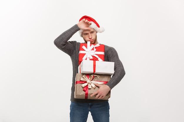 Jeune bel homme avec barbe tenant des cadeaux lourds avec une expression faciale épuisée sur blanc