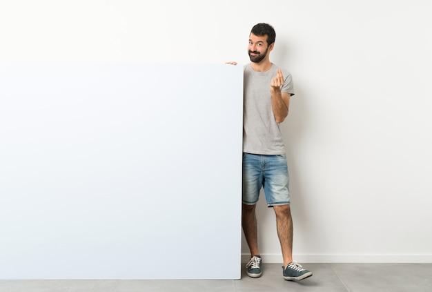 Jeune bel homme à la barbe tenant une grande pancarte bleue vide faisant un geste d'argent