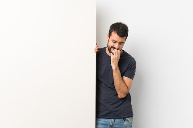 Jeune bel homme à la barbe tenant une grande pancarte vide ayant des doutes