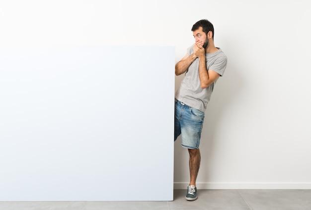 Jeune bel homme à la barbe tenant une grande pancarte vide bleue couvrant la bouche et regardant sur le côté