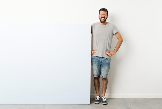 Jeune bel homme à la barbe tenant une grande pancarte vide bleue crier à l'avant avec la bouche grande ouverte