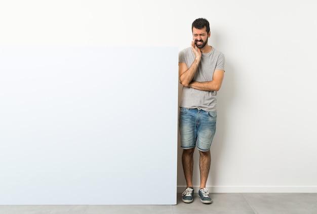 Jeune bel homme à la barbe tenant une grande pancarte vide bleue avec maux de dents