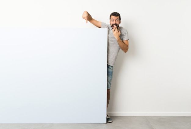 Jeune bel homme à la barbe tenant une grande pancarte vide bleue et en la pointant