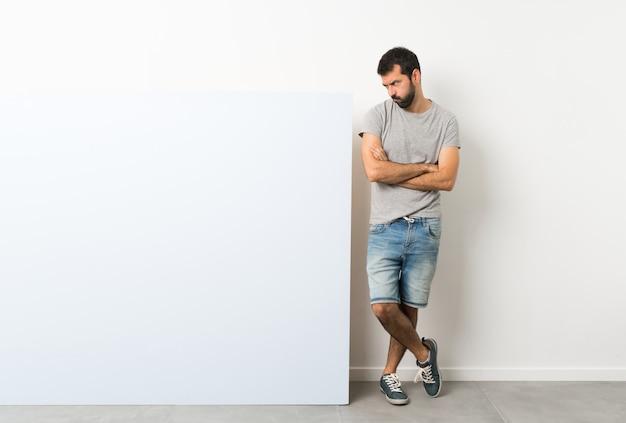 Jeune bel homme à la barbe tenant une grande pancarte vide bleue se sentir contrarié