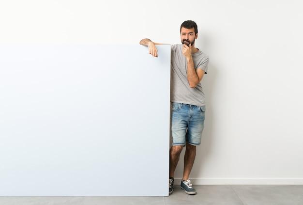 Jeune bel homme à la barbe tenant une grande pancarte vide bleue