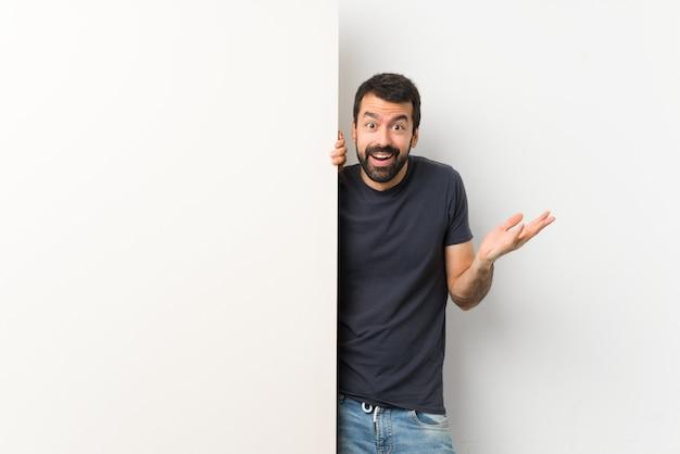Jeune bel homme à la barbe tenant une grande pancarte vide avec une expression faciale choquée