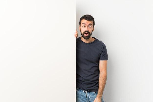 Jeune bel homme à la barbe tenant une grande pancarte vide avec une expression faciale surprise