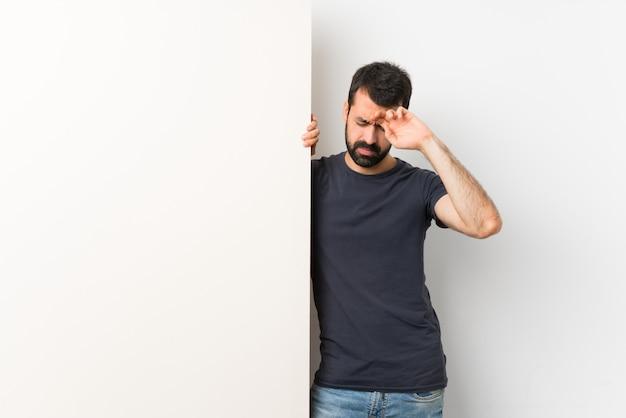 Jeune bel homme à la barbe tenant une grande pancarte vide avec expression fatiguée et malade