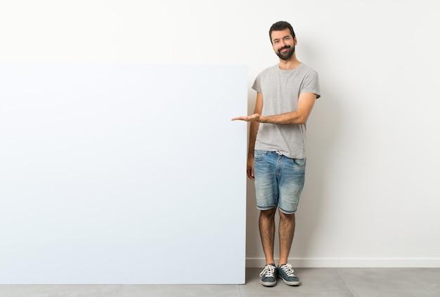 Jeune bel homme à la barbe tenant une grande pancarte vide présentant une idée