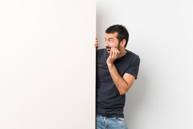 Jeune bel homme à la barbe tenant une grande pancarte vide avec surprise et expression faciale choquée