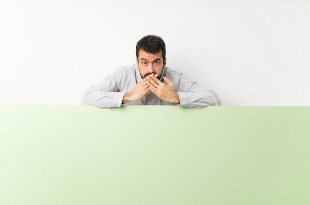 Jeune bel homme avec barbe tenant une grande pancarte vide verte couvrant la bouche avec les mains