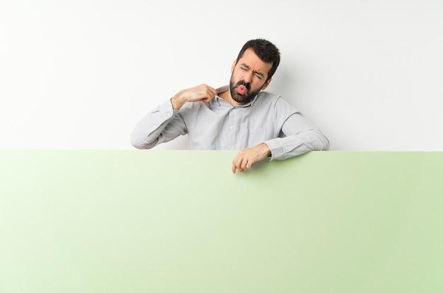 Jeune bel homme à la barbe tenant une grande pancarte vide verte avec une expression fatiguée et malade