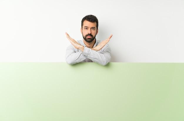 Jeune bel homme à la barbe tenant une grande pancarte vide verte ne faisant aucun geste