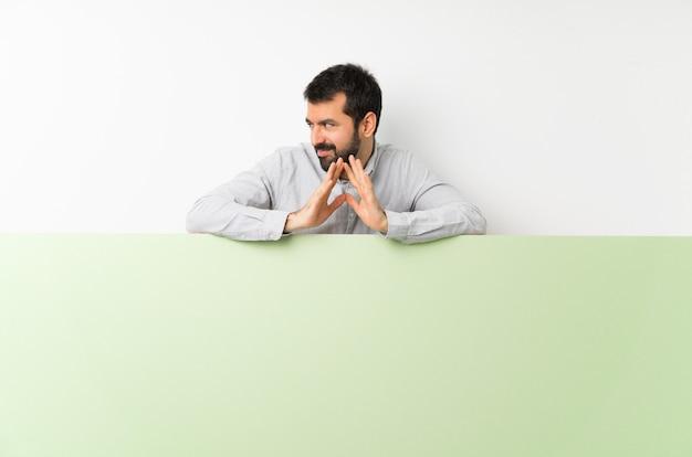 Jeune bel homme à la barbe tenant une grande pancarte vide verte scheming quelque chose