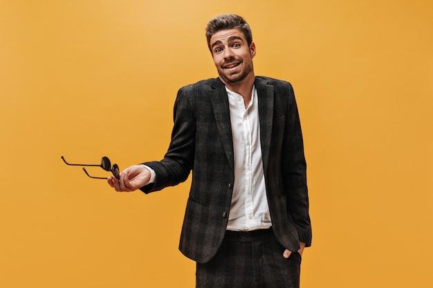 Jeune bel homme barbu en costume à carreaux et chemise blanche tient des lunettes et hausse les épaules sur un mur orange.