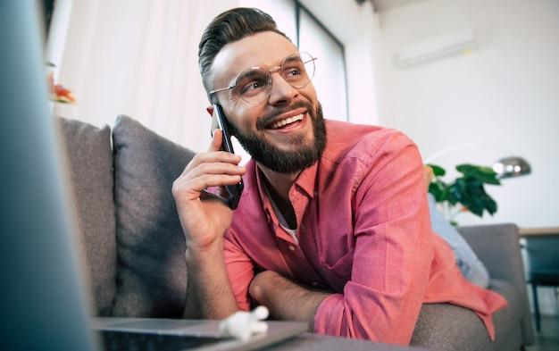 Jeune bel homme barbu heureux dans des verres utilise un smartphone pour surfer sur le net, en tapant