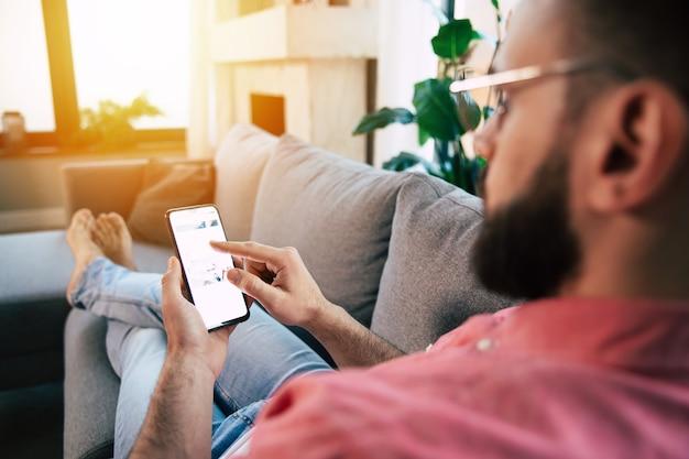 Jeune bel homme barbu heureux dans des verres utilise un smartphone pour surfer sur le net
