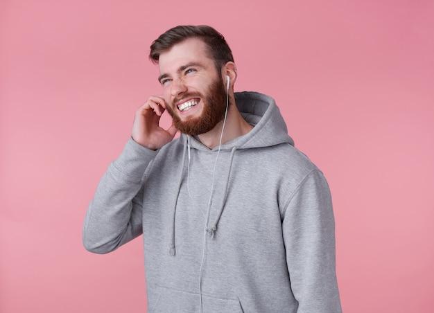 Jeune bel homme barbu rouge positif en sweat à capuche gris, a l'air heureux et sourit largement, riant et parle avec ses amis au casque, se dresse sur fond rose.