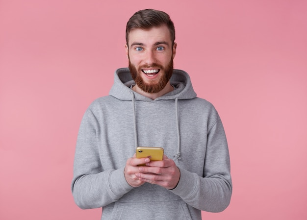 Jeune bel homme barbu rouge positif en sweat à capuche gris, semble heureux et sourit largement, tenant un smartphone, se dresse sur fond rose.