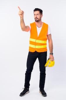 Jeune bel homme barbu travailleur de la construction isolé contre le mur blanc