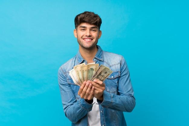 Jeune bel homme sur bleu isolé prenant beaucoup d'argent