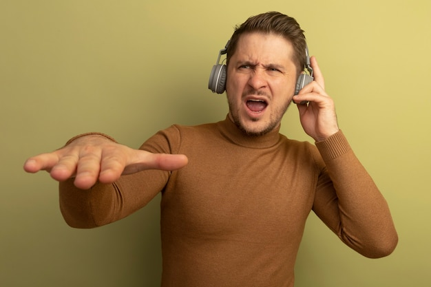 Jeune bel homme blond agacé portant et touchant des écouteurs gardant la main dans l'air en regardant de côté