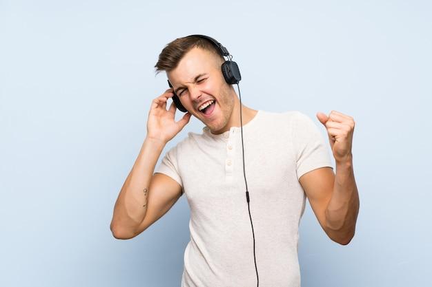 Jeune bel homme blond sur bleu isolé, écouter de la musique avec des écouteurs