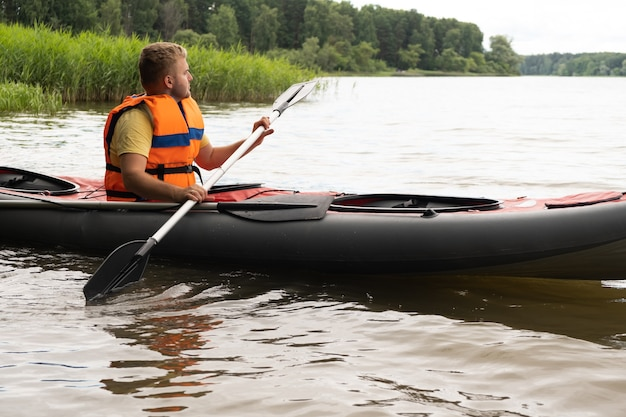Jeune bel homme blond caucasien en canoë-kayak, barque, portant un gilet de sauvetage orange, un gilet. idée de passer du temps à l'extérieur dans la nature, la forêt verte, l'été, sur le lac ou la sécurité aquatique, le divertissement.