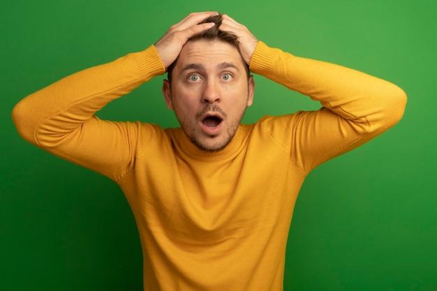 Jeune bel homme blond concerné regardant droit en mettant les mains sur la tête isolée sur un mur vert